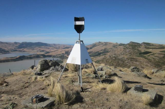 Photo of a survey mark on hilltop with Lyttelton Harbour in the background
