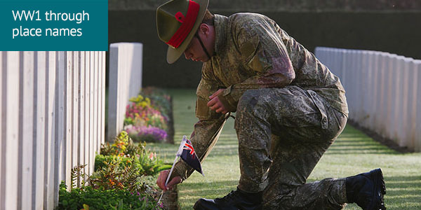 PTE Samuel Appleton places an New Zealand flag by a headstone a Buttes New British Cemetery, Belgium