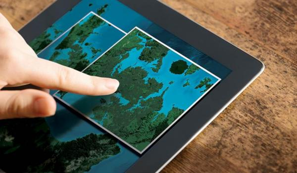 Topo Strategy 2015 - person pointing at maps on a tablet